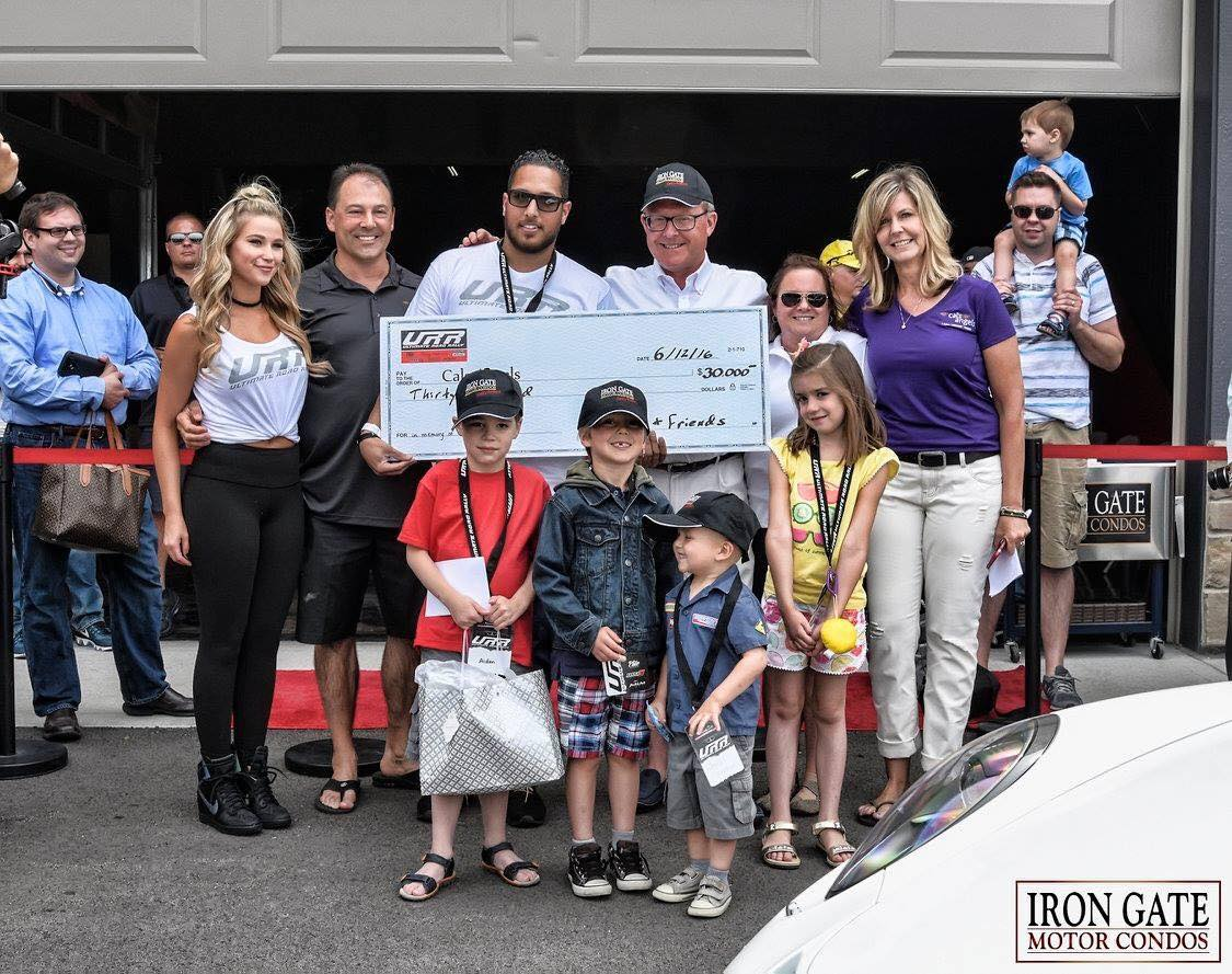 Omar & Iron Gate Motor Condos founder Tom Burgess present the Cal's Angels with a check for $30,000