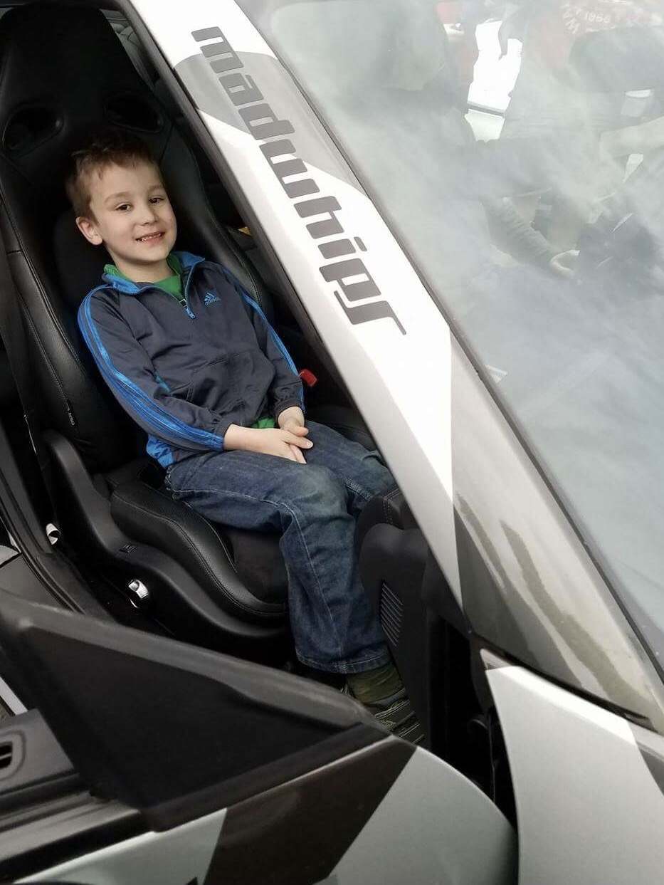 A young GoldRush Rally fan sits in Tim Hayes Alpha 7 Nissan GT-R